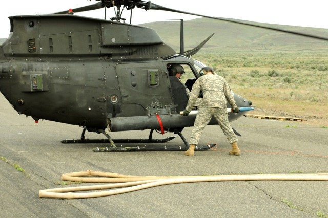 Staff Sgt. David Chapman, 5th Mobile Public Affairs Office Cutline: Ground crews load rockets onto a OH-58D before they head to the sky and provide air support for a four truck convoy during a live fire exercise at Yakima Training Area, May 11.