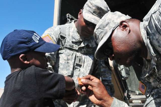 Sgt. Deon Lee, a medic with 3rd Battalion, 82nd Field Artillery Regiment, 2nd Brigade Combat Team, 1st Cavalry Division, applies a bandage to Robert MacDonald Jr., 5, son of Chief Warrant Officer 2 Robert MacDonald, a target acquisition platoon leader