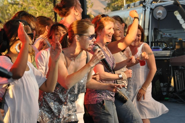 Spouses of Fort Irwin Soldiers dance onstage with singer Julie Dutchak during the Lt. Dan Band's concert May 14 at Fort Irwin's Army Field.