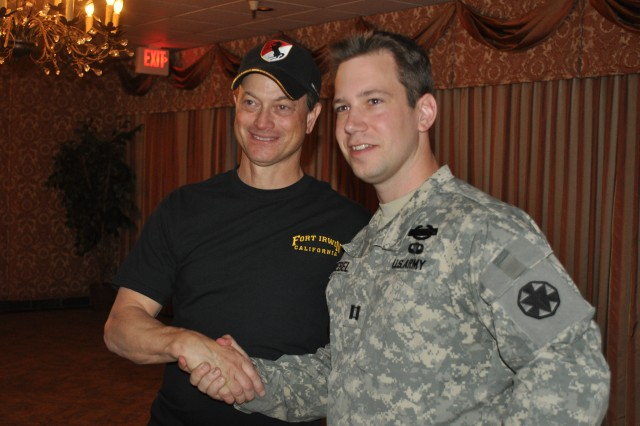 Gary Sinise shakes hands with Capt. Zachary Knoebel of the NTC/Fort Irwin Protocol Office after a Lt. Dan Band concert at Fort Irwin May 14.