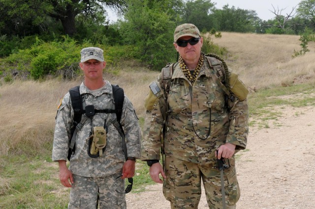 FORT HOOD, Texas-Staff Sgt. Riley Walker (left) and Mike Greguras, both instructors for the Combat Tracker Course stop along side the road after hiking several miles to leave foot prints and other identify markers called 'spoor' for the tracker