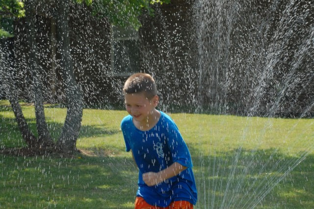 Owen Sonnenberg, 8, runs through the sprinkler in his yard at Redstone Communities. Part of the appeal of the homes offered through military housing is the yard space, according to Ray Zapata, chief of the housing division in Directorate of Public Works.