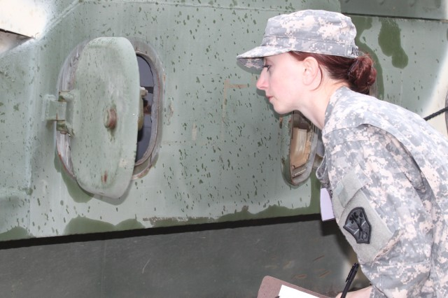 Pfc. Kira Anderson, a Multi-Media Illustrator with Delta Company, 203rd Military Intelligence Battalion, Military Intelligence Readiness Command, searches an 'enemy' vehicle during the Combined Joint Captured Materiel Exploitation Center