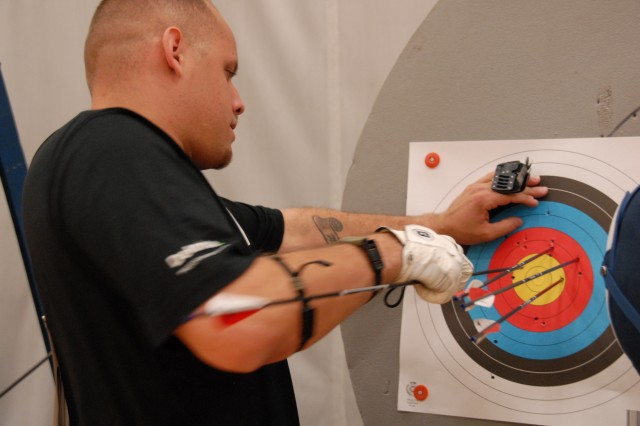 Staff Sgt. Curtis Winston retrieves his arrows from a target during the Archery preliminaries at Sports Center I, Olympic Training Center in Colorado Springs, Colo.