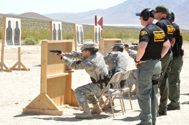 Trainers from the Los Angeles County Sherriff's Department watch as Soldiers from the National Training Center Military Police Company take part in a shooting exercise designed to simulate shooting out of a patrol car during the company's