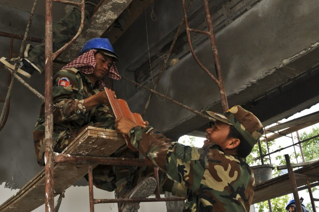 Cambodian engineers serving with the National Peacekeeping Force, Mines and Explosive Remnants of War Clearance, Royal Cambodian Armed Forces, pass ceramic roofing tiles through the ceiling of a new school being built in the village of Taing Sia May 16