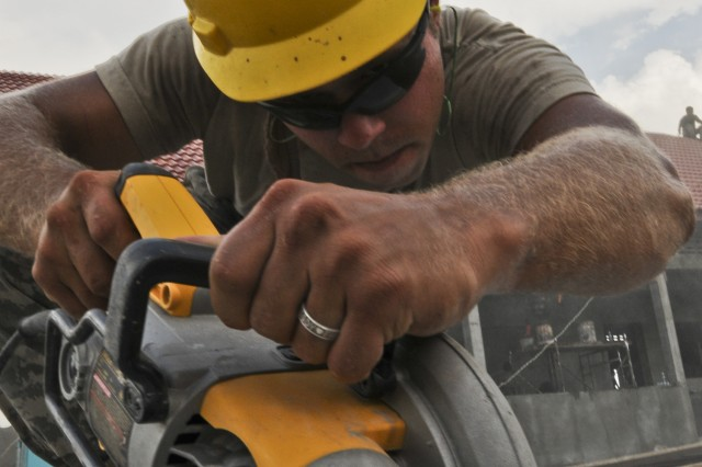 Spc. Cody Gange of Mt. Vernon, Mo., who serves with 544th Engineer Company, 52nd Eng. Battalion, 555th Brigade, cuts gypsum board on the construction site of a new school in the village of Taing Sia May 16 during exercise Angkor Sentinel 2011. The school