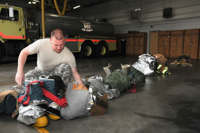 Sgt. Larry Rhodes with the 63rd Ordnance Fire Company attached to Fire Station 105 inspects his firefighting safety equipment.