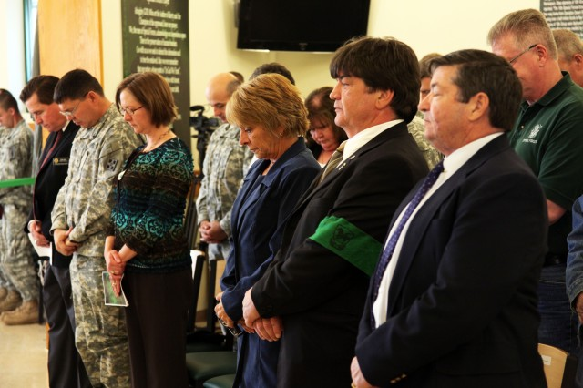 FORT CARSON, Colo. -- Audience members bow their heads during a prayer at the opening of the renovated 10th Special Forces Group (Airborne) dining facility. Ellen LaRochelle, center, spoke at the ceremony, which honored her late husband, Master Sgt. Mark
