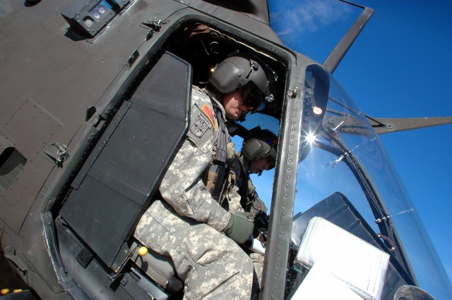 Chief Warrant Officer 2 Nicholas Willden and Cpt. Wesley Cogdal, pilots from Cajun Troop, 4th Squadron, 6th Air Cavalry Regiment, get ready to fly their OH-58D Kiowa helicopter during their annual gunnery qualifications at Yakima Training Center,