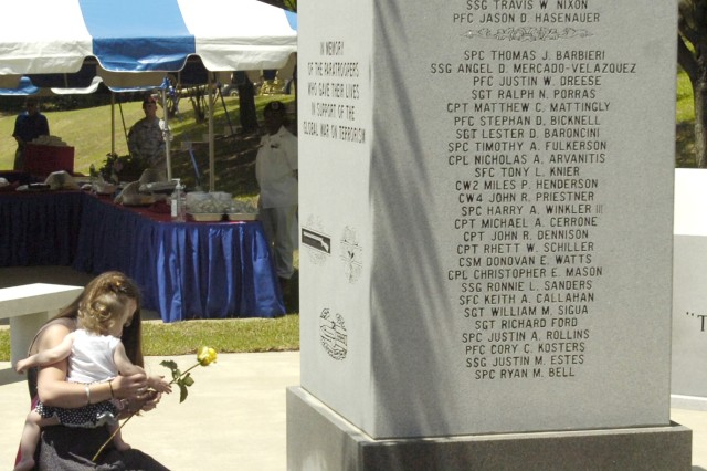 Fort Bragg, NC - Gold Star families, those that have lost loved ones in combat put yellow roses at the base of the Global War on Terrorism Memorial as the names of their loved ones are recited at the 82nd Airborne Division's Annual Memorial