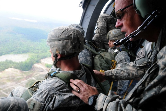 First Sgt. Jerry Tucker, C Co., 1st Battalion, 504th Parachute Infantry Regiment, 1st Brigade Combat Team, readies his next jumper for a static line jump from a UH-60 Blackhawk on May 16. Eight soldiers make up the 1/504th PIR's team for the annual