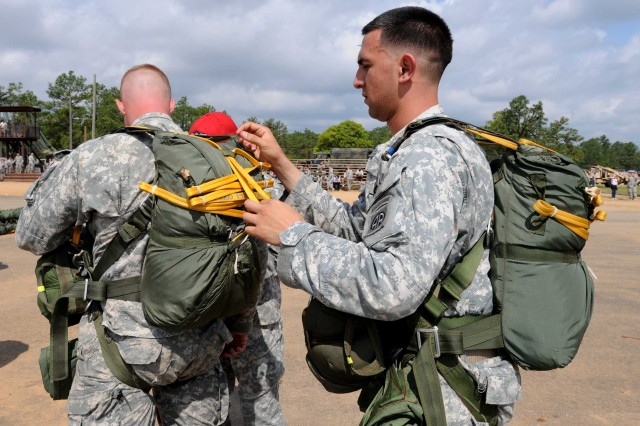 Sgt. Francisco Morelos, an infantry squad leader with C Co., 2nd Battalion, 505th Parachute Infantry Regiment, 3rd Brigade Combat Team, helps Staff Sgt. Perry Houchens, a C Co., 2/505 PIR platoon sergeant, don his parachute prior to a static line jump on