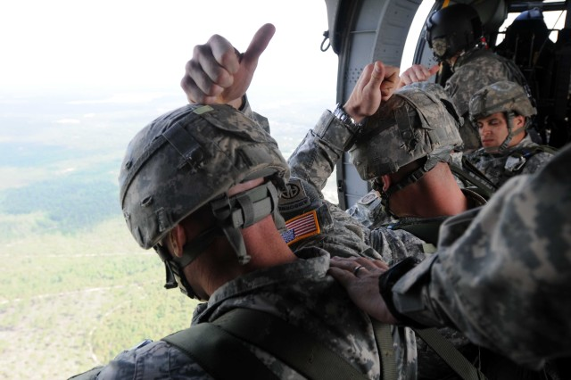 Paratroopers assigned to 1st Battalion, 504th Parachute Infantry Regiment, 1st Brigade Combat Team, signal to the jumpmaster that their equipment has been checked before conducting a static line jump from a UH-60 Blackhawk on May 16. These eight soldiers