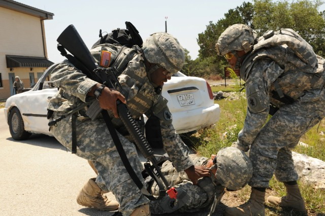 CAMP BULLIS, Texas - Sgt. Donald Richardson (left) and Sgt. 1st Class Debra McGee (right) pull Sgt. Carmen Lockett out of a mock danger zone during a U.S. Army South field training exercise here May 17.