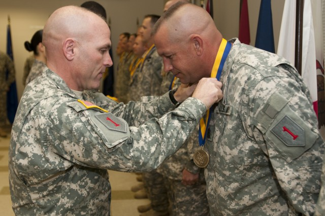 Col. Frank Muth places the Order of Saint Michael medal around the neck of First Sgt. Kevin Kramer in an induction ceremony on Fort Riley, May 19. Kramer and several other Soldiers with the Combat Aviation Brigade, 1st Infantry Division's 3rd