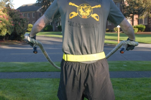 JOINT BASE LEWIS-MCCHORD, Wash. - A member of 2nd Squadron, 1st Cavalry Regiment, 4th Stryker Brigade Combat Team, 2nd Infantry Division, flexes as he holds up a length of rope, part of the Physically, Mentally, Emotionally Hard Gauntlet, also known as