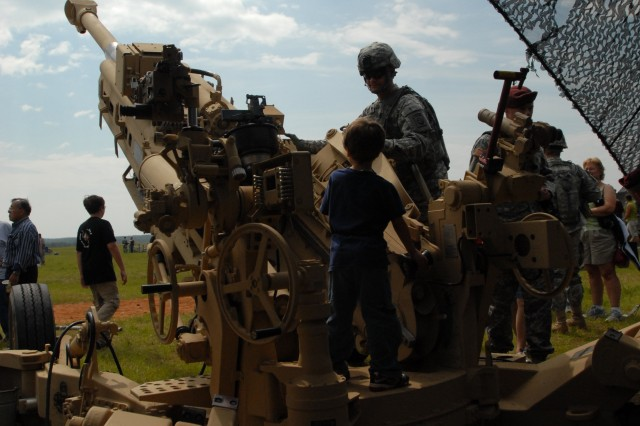 A paratrooper with the 82nd Airborne Division shows a child the M77A2 Medium Towed Howitzer May 20, during the Joint Operation Access Demonstration held at the Sicily Drop Zone, Ft. Bragg. The JOAD is the last demonstration held during the