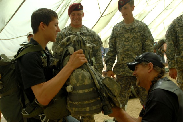 Sterling Dieken (left), and his father, Veteran and former combat engineer Ken Dieken, arrange for some weight to be added to Sterling's already unwieldy parachute rig at a demonstration, May 20th, with Paratroopers from the 2nd Battalion, 505th