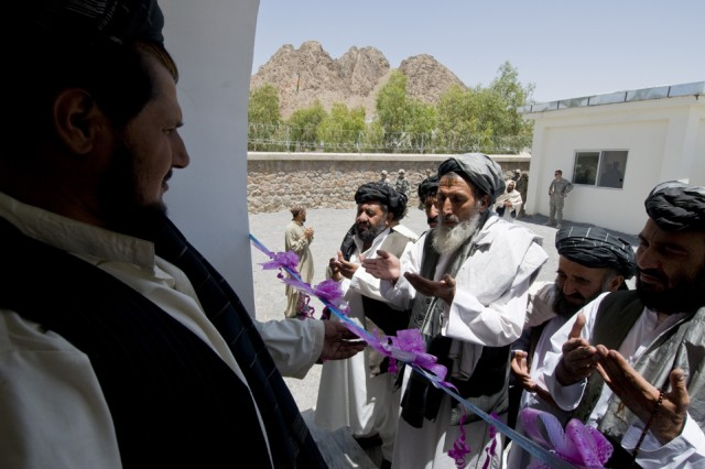 TAKTEH POL, Afghanistan - Haji Nefa, center, Takteh Pol's director of education, recites a prayer to district center members before cutting a ceremonial ribbon in front of a new mosque in the subdistrict of Takteh Pol, Afghanistan, May 16, 2011. The