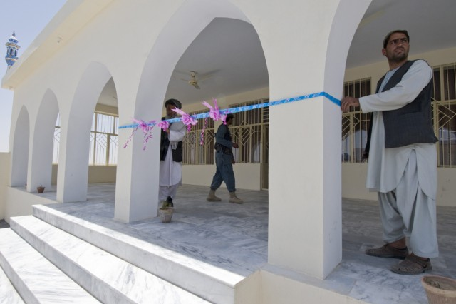 TAKTEH POL, Afghanistan - Members of the Takteh Pol shura committee tie a ribbon around the  pillars of a new mosque prior to a ribbon cutting ceremony in the subdistrict of Takteh Pol, Afghanistan, May 16, 2011. The celebration also included the opening