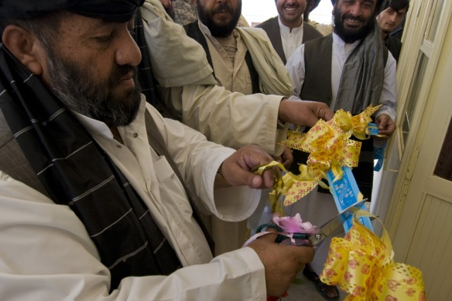 TAKTEH POL, Afghanistan - Haji Niaz Mohammed, Takteh  Pol's  shura chairman, cuts a ceremonial ribbon during the opening of a new district center in the subdistrict of Takteh Pol, Afghanistan, May 16, 2011. A ribbon cutting ceremony was also held