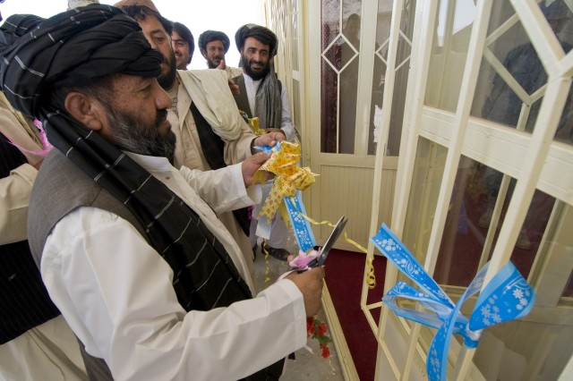 TAKTEH POL, Afghanistan - Haji Niaz Mohammed, Takteh Pol shura chairman, cuts a ceremonial ribbon during the opening of a new district center in the subdistrict of Takteh Pol, Afghanistan, May 16, 2011. A ribbon cutting ceremony was also held signifying