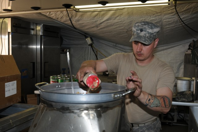Spc. James Bradbury, noncommissioned officer in charge of the containerized kitchen, Headquarters Headquarters Company, 296th Brigade Support Battalion, adds seasoning to a pot of mixed vegetables while preparing dinner for approximately 500 Soldiers of