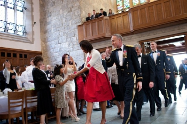 First Lady Michelle Obama shakes hands with a young girls as she enters the West Point Graduation Banquet at the United States Military Academy in West Point, New York, May 20, 2011. Mrs. Obama is escorted by Lt. Gen. David Huntoon, superintendent at the