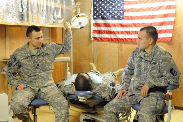 Twin brothers and Army dentists, Capt. Aleksandr Baron and Capt. Dmitry Baron, look over a patient at the dental clinic on Contingency Operating Site Kalsu, Iraq, May 6, 2011.  The men are both augmenting 3rd Armored Cavalry Regiment at two different
