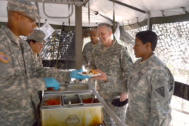 Brig. Gen. Ronald Dziedzicki (center), deputy commander for the 3rd Medical Command (Deployment Support) stands patiently as he is served lunch by the food service workers of the 429th Multifunctional Medical Battalion (MMB) May 7. The MMB was