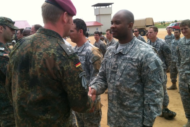 Staff Sgt. Michael Hammitt, an electronic maintenance noncommissioned officer with 3rd Special Forces Group (Airborne), receives his silver German airborne wings from 1st Lt. Marc Breitenfeld, jumpmaster commander with the German Army's 31st