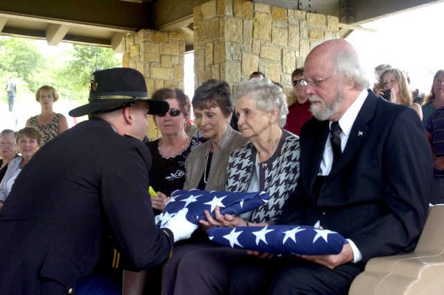 DALLAS  - Capt. Ray Mattia, rear detachment commander of 3rd Battalion, 8th Regiment, 1st Cavalry Division, hands a US flag to Lucille Crowder, cousin of Private 1st Class Joseph A. Terrell, during a repatriation ceremony in Terrell's honor.