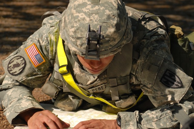 U.S. Army Spc. Michael Perez-Arce, a native of Lower Lake, Calif., and an MP with the 615th Military Police Company, looks over his coordinates during the daytime land navigation portion of the 18th Military Police Brigade's Warrior and Warrior