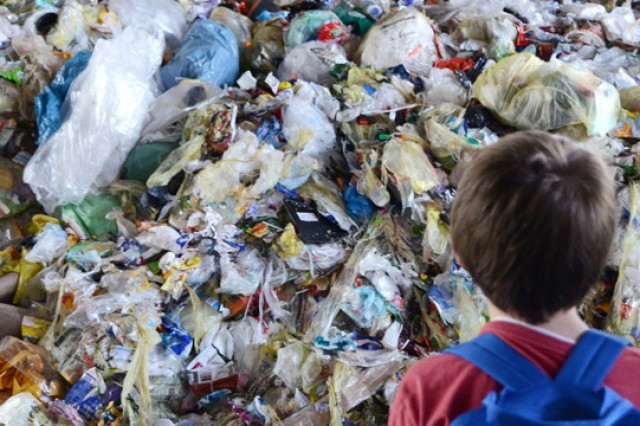 Grafenwoehr Elementary fourth-grader Xander Mattkins inspects a large pile of recyclable plastics before it is sorted during a field trip to the Bergler Sorting Plant in Steinfels, Germany.