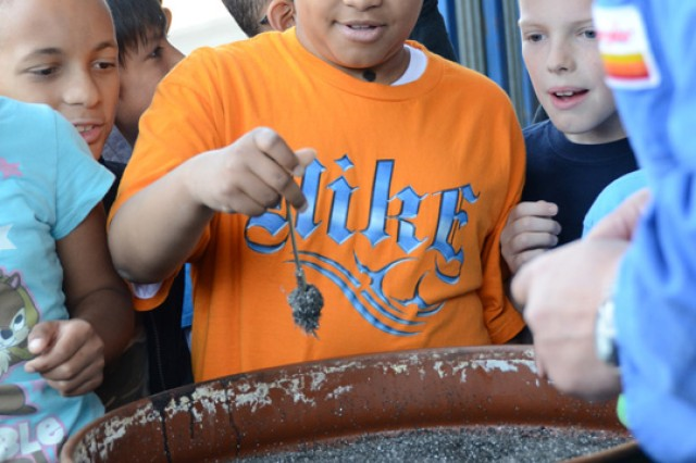 Michael Clark, a fourth-grader at Grafenwoehr Elementary, tests the magnetic value of the recycled metal during a field trip to the Bergler Sorting Plant in Steinfels, Germany.