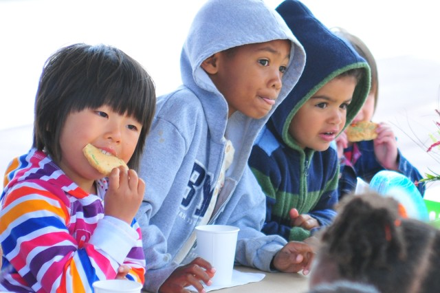 PRESIDIO OF MONTEREY Calif. Aca!A? Children share a secret and enjoy their Mother's Day party snacks. Monterey Road Child Development Center preschoolers invited their moms to an early Mother's Day celebration at the center May 6.