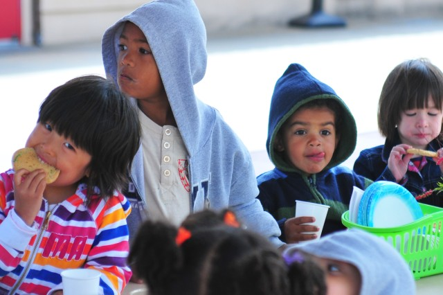 PRESIDIO OF MONTEREY Calif. Aca!A? Children enjoy their Mother's Day party snacks a mom looks on. Monterey Road Child Development Center preschoolers invited their moms to an early Mother's Day celebration at the center May 6.