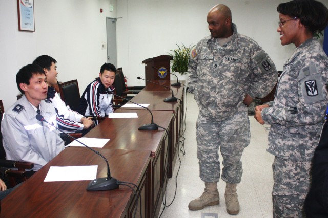Sgt. Randi Choice of D Battery 6-52nd ADA Battalion (right) and Staff Sgt.Thomas Levi of C Btry 6-52 ADA Battalion (middle) provide English conversation lessons  to members of the Suwon Seobu KNP police station every Thursday.