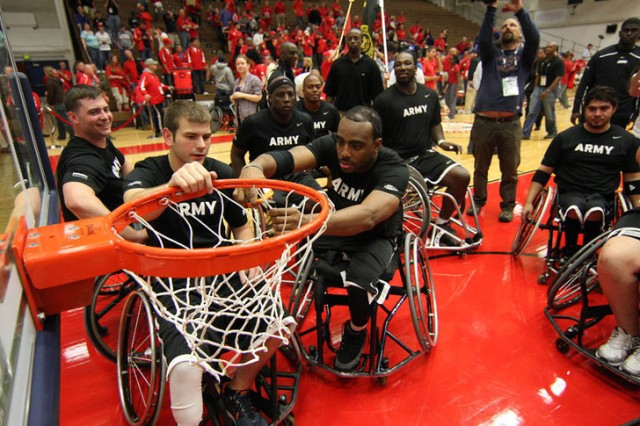 The Army wheelchair basketball team cuts down the net after defeating the Marine Corps to win gold.