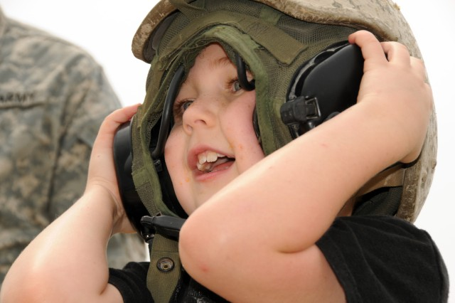 A visitor tries on the crew helmet aboard the Abrams M1A2 SEPv2 tank that was on display May 20 during the 2011 Joint Service Open House at Joint Base Andrews Md.