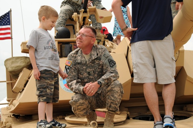 Master Sgt. Herbert Mowrey 2-8 Cav. 1st BCT 1st Cav. Div. talks with a youth about the Abrams M1A2 SEPv2 tank that was on display May 20 during the 2011 Joint Service Open House at Joint Base Andrews Md.