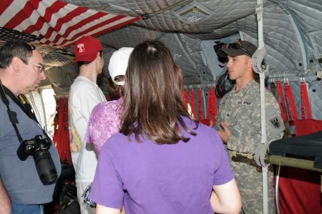 Sgt. Michael Hammer 5-159 Avn. Regt. 244th Avn. Bde. 11th Avn. Cmd. walks with visitors about the CH-47D Chinook helicopter  May 20 during the 2011 Joint Service Open House at Joint Base Andrews Md.
