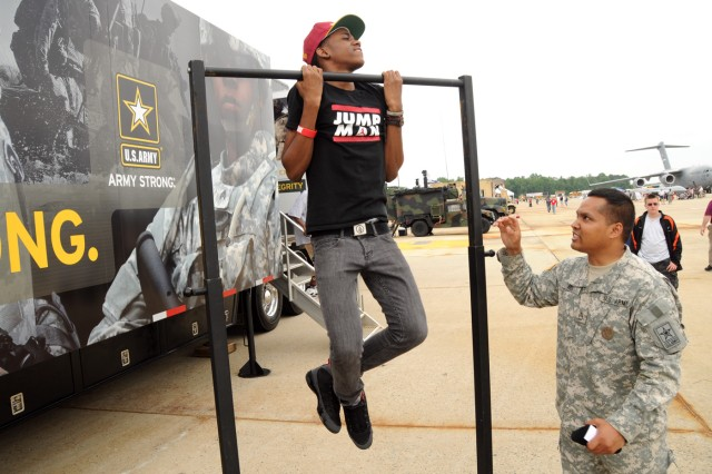Sgt. 1st Class Rithy Ros 1st Recruiting Battalion Baltimore Md. challenges a student and potential recruit on the pull-up bar May 20 during the 2011 Joint Service Open House at Joint Base Andrews Md.