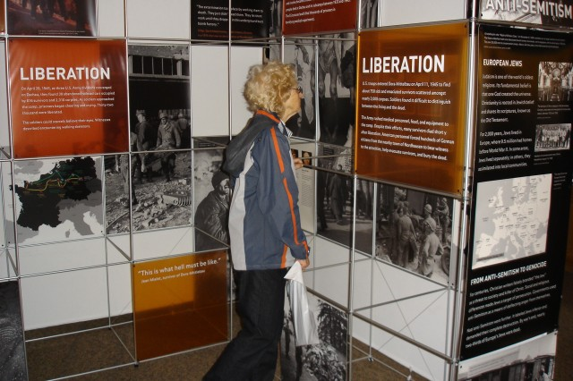 """An Open House visitor (left) views the educational Holocaust exhibit, """"One Soul: When Humanity Fails."""""""