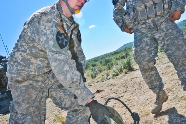 Spc. Gerald Lacy (left) and Spc. Scott Kennon, both members of Headquarters Platoon, Company C, 2nd Battalion, 3rd Infantry Regiment, make light of an otherwise mundane task at Yakima Training Center, Wash., May 24 while packing up their equipment for rel