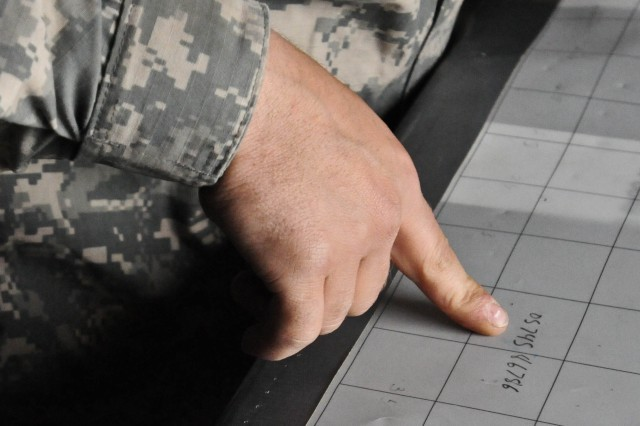 Pfc. Bronson Koeber, a chart operator with 2nd Platoon, Battery A, 1st Battalion, 37th Field Artillery Regiment, plots coordinates on a large chart of paper with grid lines and a long steel ruler May 21 at Yakima Training Center in Central Washington Stat