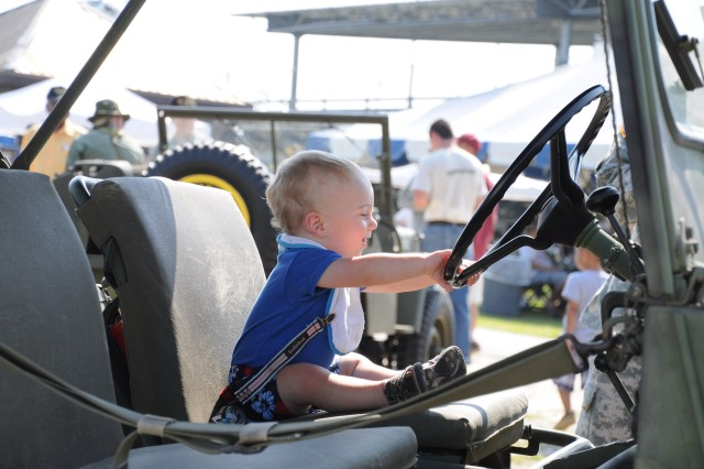 Dylan Horst, 1, takes the wheel of a M-151A2 military utility tactical truck. The vehicle, provided by the Celebrate Freedom Foundation, was one of many static displays at Hilton Field Saturday for Armed Forces Day. The interactive displays highlighted di