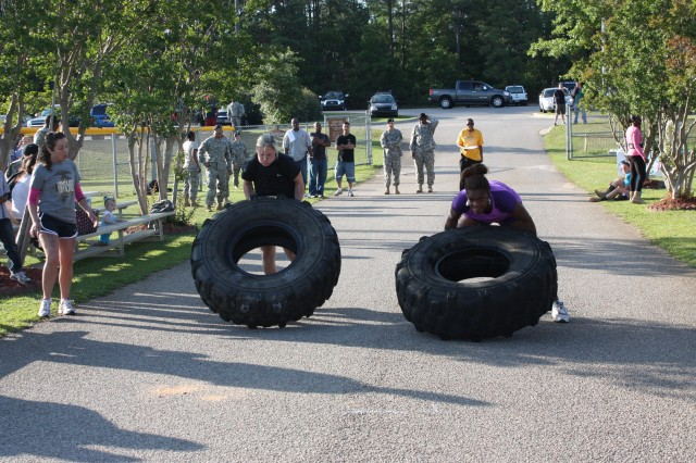Nicole Hayman, left, with the Training Support Battalion, flips a tire during last week's competition.