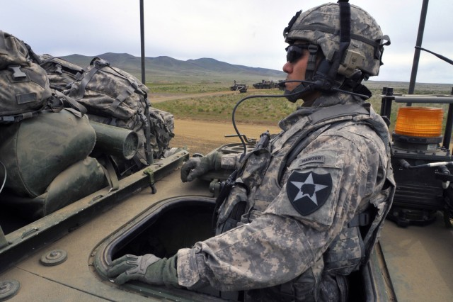Cpt. Don Kanase, company commander, Bravo Company, 2nd Battalion, 3rd Infantry Regiment, looks on from the rear hatch of his Stryker as his fleet of Strykers files down a rugged, dirt road at Yakima Training Center, Washington May 21.  2-3 is training and